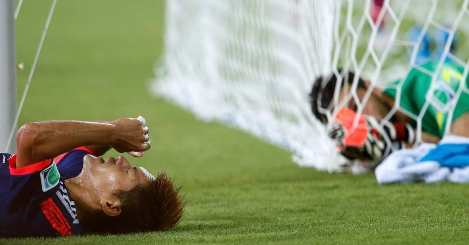 Yoshito Okubo fica no chão após finalização enquanto o goleiro grego Orestis Karnezis tenta se soltar das redes do gol