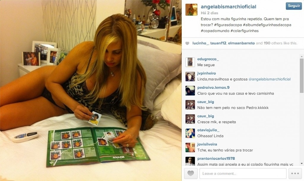 20.jun.2014 - Ângela Bismarchi, de lingerie, cola figurinhas no seu álbum da Copa