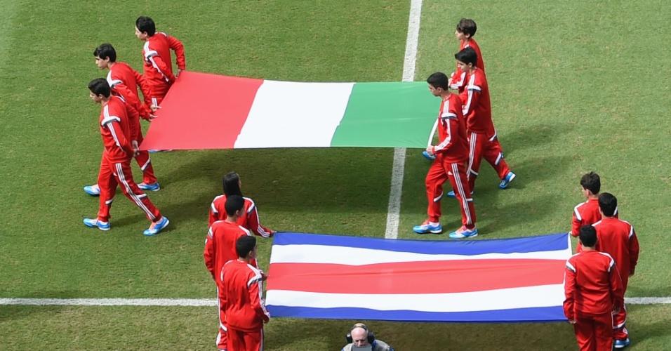 Bandeiras de Itália e Costa Rica são levadas para o campo antes da execução dos hinos nacionais