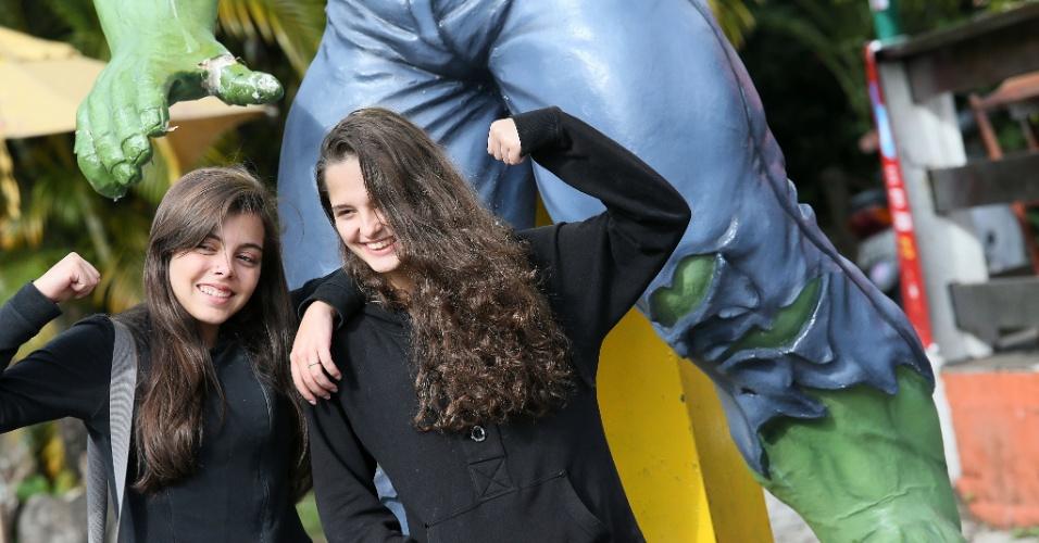 Duas garotas posam para foto ao lado da estátua do Hulk, em um restaurante próximo à Granja Comary