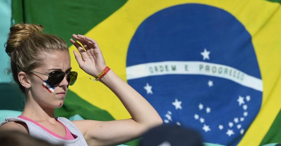 Em frente a bandeira brasileira, torcedora com rosto pintado com as cores da França aguarda a partida contra a Suíça