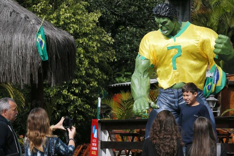 Garotinho se diverte com a estátua do Hulk
