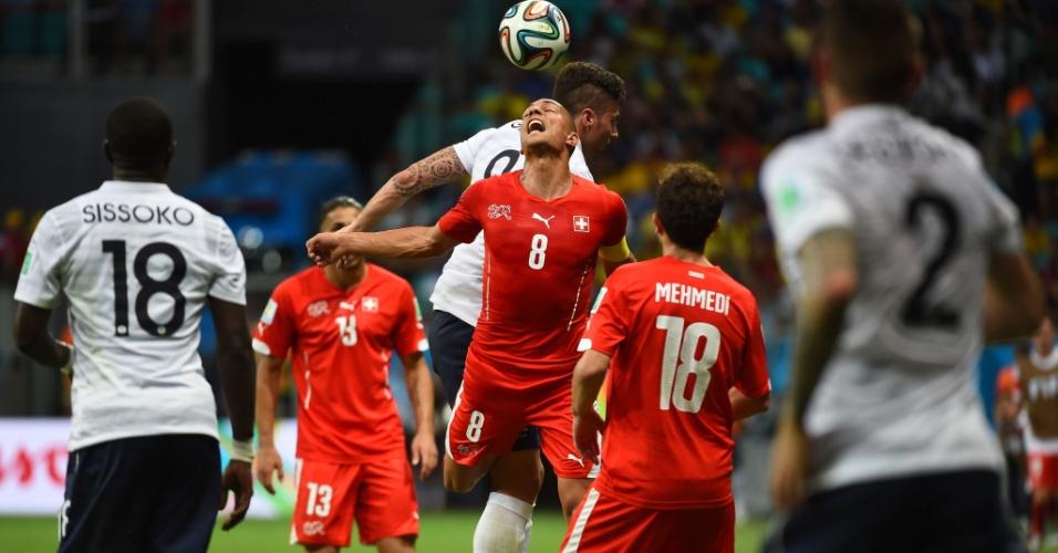 Goekhan Inler, camisa 8 da Suíça, divide a bola de cabeça com francês durante a partida na Fonte Nova