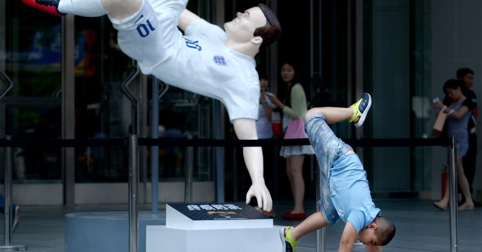 Sem sucesso, garotinho tenta imitar movimento do boneco do inglês Wayne Rooney, em um shopping de Pequim, na China