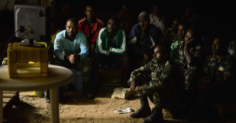 Soldados etíopes, em missão na Somália, assistem à partida entre Colômbia e Costa do Marfim em uma televisão improvisada