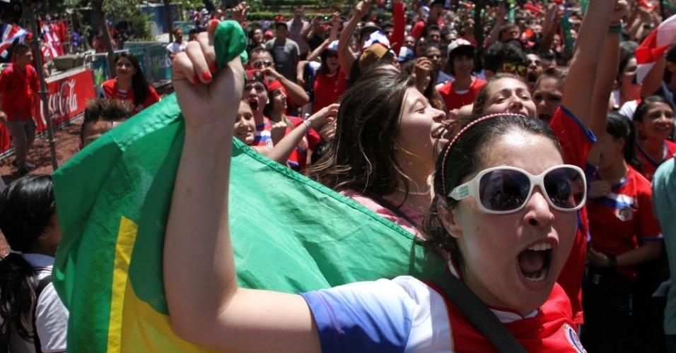 Torcedora da Costa Rica comemora vitória sobre a Itália com bandeira do Brasil nas costas