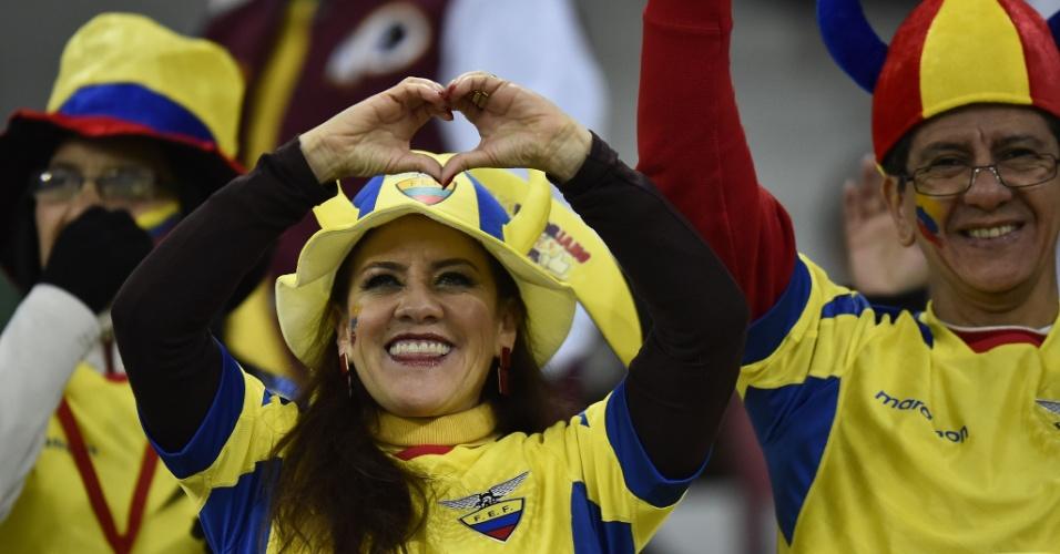 Torcedora da seleção equatoriana faz sinal de coração para a câmera antes do início do jogo contra Honduras