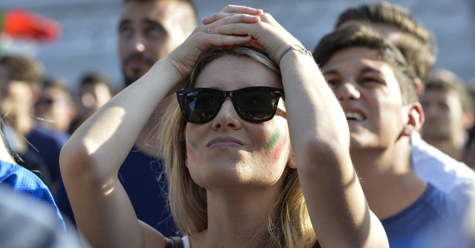 Torcedora faz cara de surpresa acompanhando a Itália enfrentar a Costa Rica na Piazza Venezia, em Roma