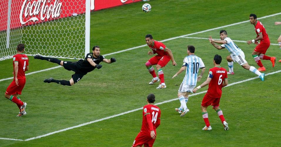 Alireza Haghighi para socar a bola na área do Irã durante a partida entre Argentina e Irã