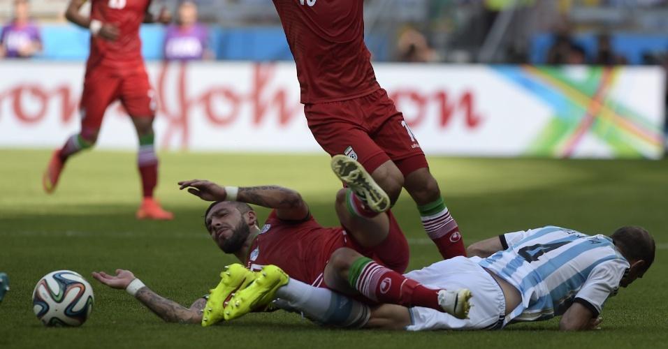 Ashkan Dejagah e Pablo Zabaleta caem após forte disputa de bola durante a partida entre Argentina e Irã