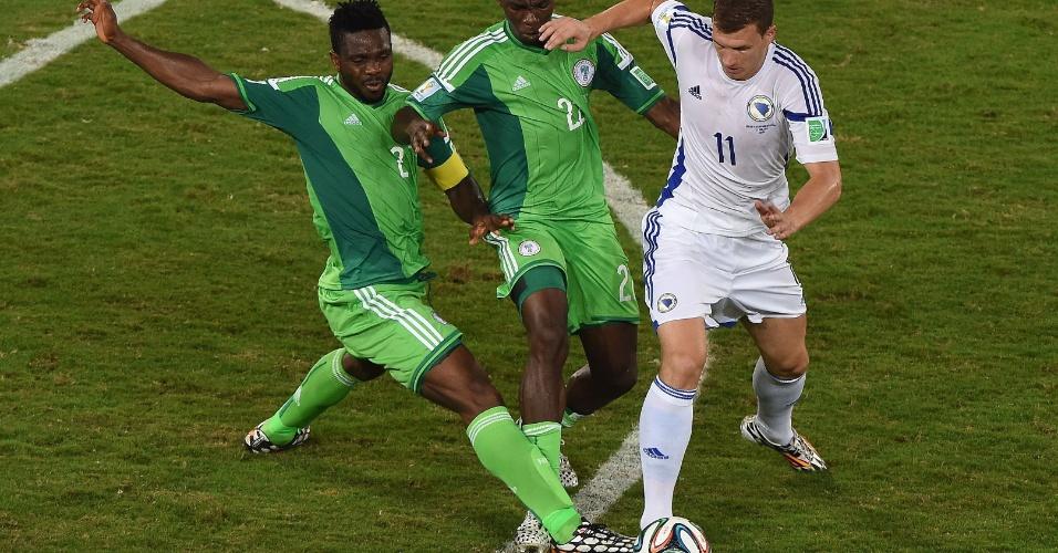 Edin Dzeko, da Bósnia, protege a bola entre dois marcadores nigerianos