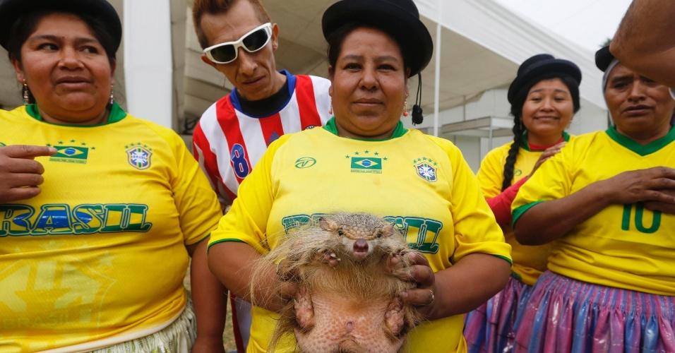 Em Lima, no Peru, tatu-bola é exibido por uma mulher antes de uma partida de futebol no mercado local