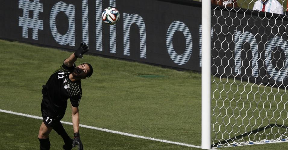 Goleiro Alireza Haqiqi, do Irã, voa para tentar fazer a defesa durante a partida entre Argentina e Irã