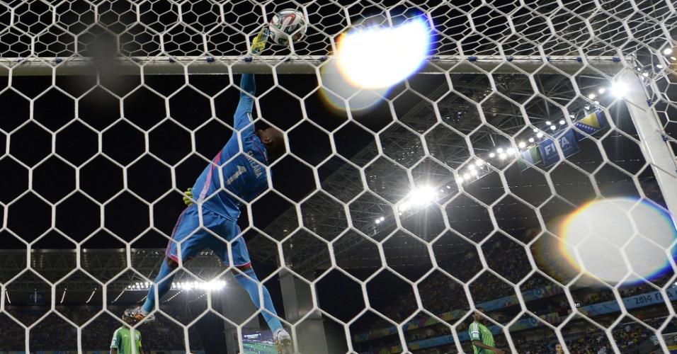 Goleiro Vincent Enyeama salta alto para alcançar a bola e salvar a Nigéria