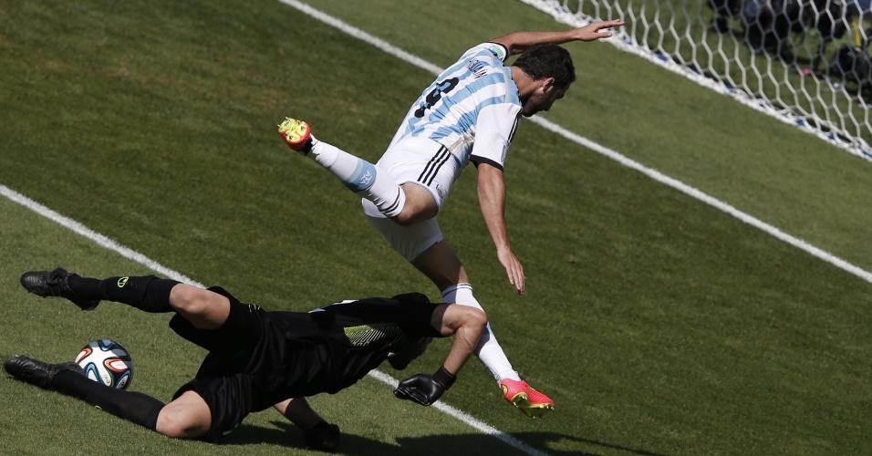 Gonzalo Higuain cai após disputa de bola com o goleiro Alireza Haqiqi durante a partida entre Argentina e Irã