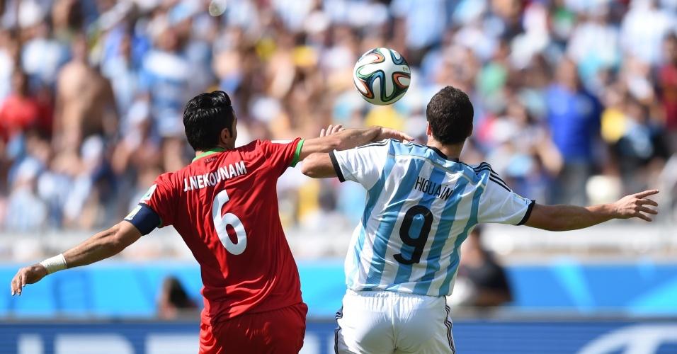 Javad Nekounam e Gonzalo Higuain disputam bola pelo alto durante a partida entre Argentina e Irã