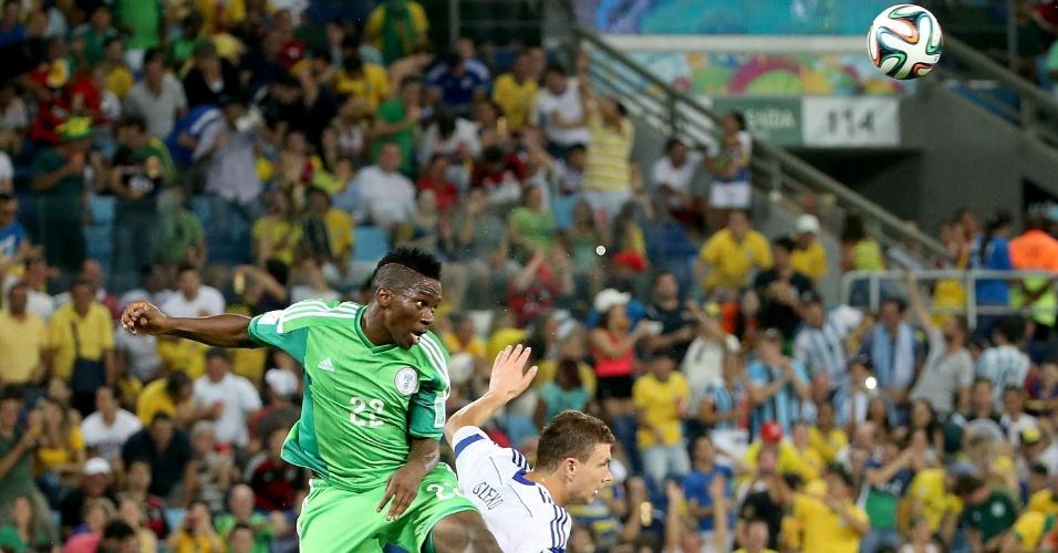 Kenneth Omeruo, da Nigéria, salta com Edin Dzeko, da Bósnia, durante partida na Arena Pantanal