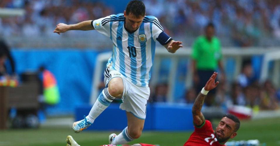 Lionel Messi pula para escapar de carrinho de Ashkan Dejagah durante a partida entre Argentina e Irã