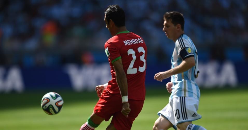 Mehrdad Pooladi chuta a bola enquanto é observado de perto por Lionel Messi