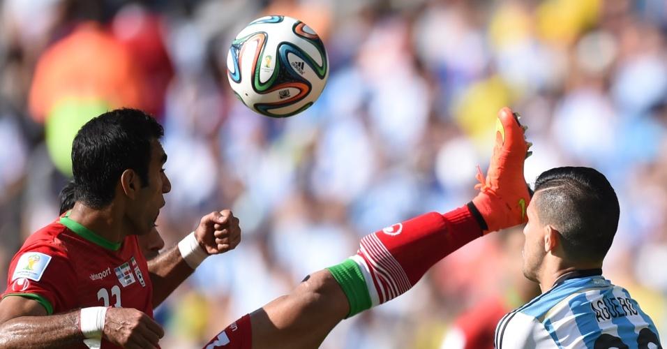 Mehrdad Pooladi e Sergio Aguero disputam bola pelo alto durante a partida entre Argentina e Irã