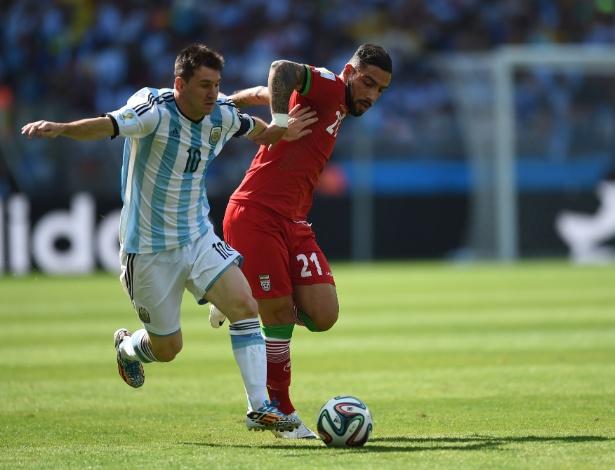 Messi tenta escapar da marcação de Ashkan Dejagah durante a partida entre Argentina e Irã