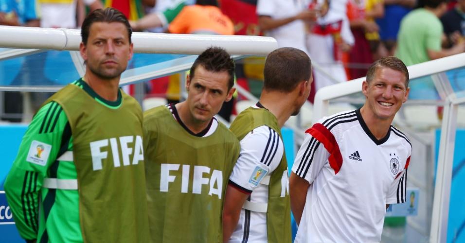 Schweinsteiger (à direita) sorri no banco de reservas da Alemanha antes do jogo contra Gana, no Castelão