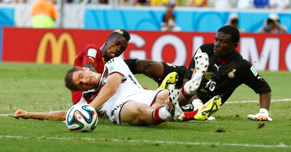 21.jun.2014 - Thomas Müller, da Alemanha, divide a bola na área de Gana e fica caído no gramado do Castelão
