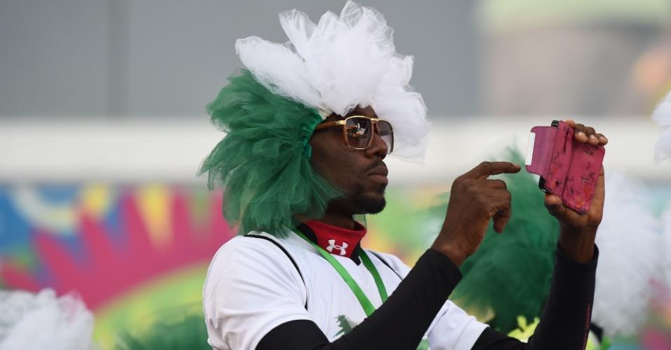Torcedor com peruca nas cores da Nigéria aproveita para fazer registros com o celular antes do início do jogo
