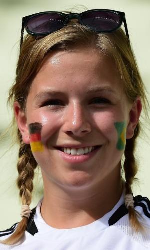 Torcedora com as bandeiras de Alemanha e Brasil no rosto sorri antes do jogo contra Gana, no Castelão