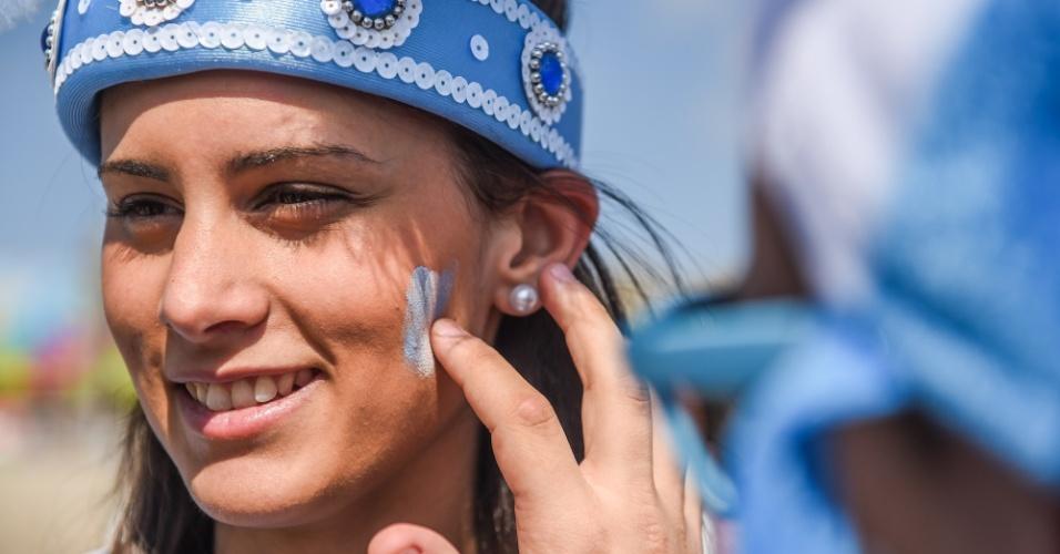 Torcedora pinta o rosto com as cores da bandeira argentina antes do jogo contra o Irã