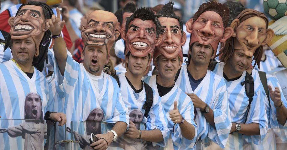 Torcedores argentinos usam máscaras com o rosto dos jogadores para o jogo contra o Irã no Mineirão