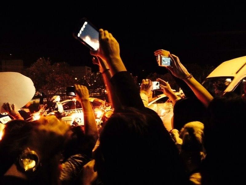 Torcedores se esticam para conseguir uma foto ou vídeo da chegada da seleção em Brasília