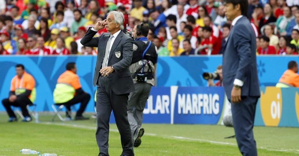 22.jun.2014 - Cercado de garrafas de água, técnico da Argélia, Vahid Halilhodzic (ao fundo), orienta seus atletas no jogo contra a Coreia do Sul