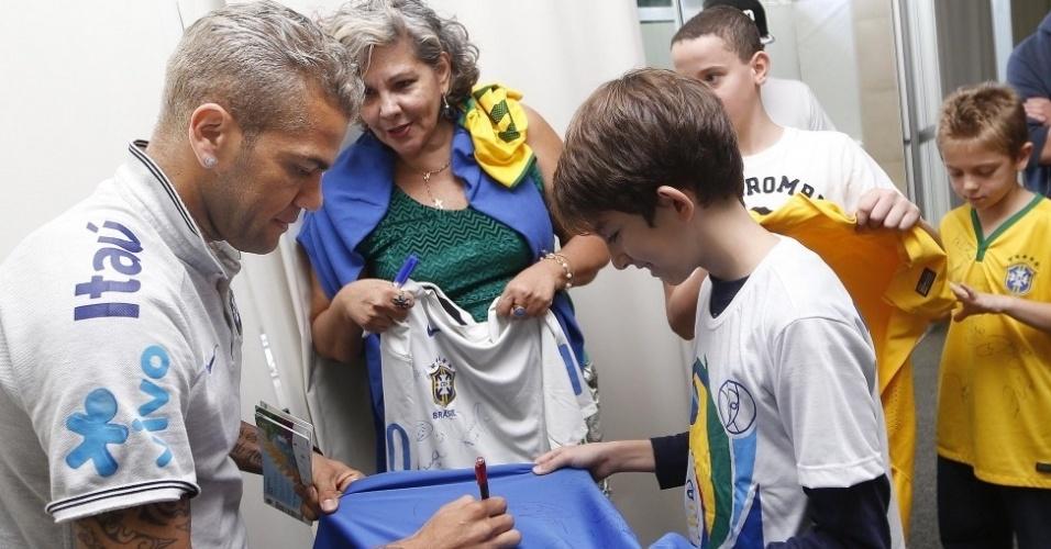 Daniel Alves autografa camiseta em Brasília. Jogadores receberam a visita de familiares e amigos em uma área reservada fora do hotel em que a equipe está concentrada