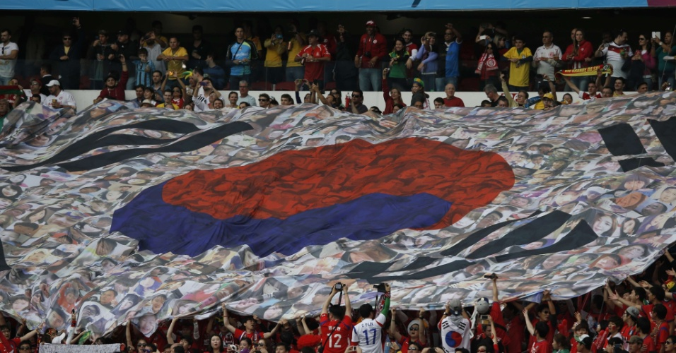 22.jun.2014 - Sul-coreanos seguram bandeira gigante no início da partida contra a Argélia, no Beira-Rio