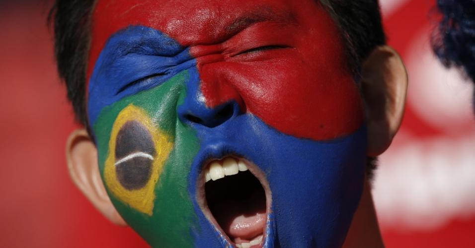 22.jun.2014 - Torcedor pintado com as cores da Coreia do Sul e do Brasil vibra antes da partida contra a Argélia