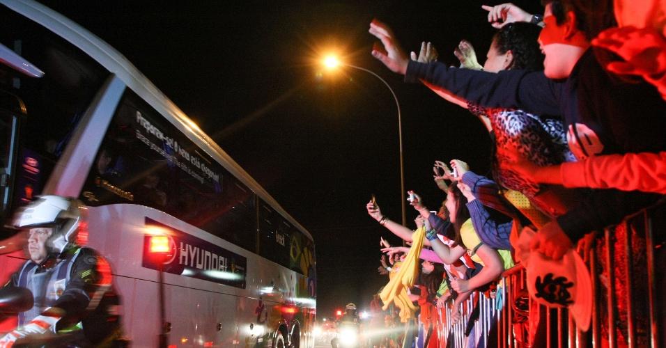 Torcedores acenam para o ônibus da seleção brasileira em Brasília