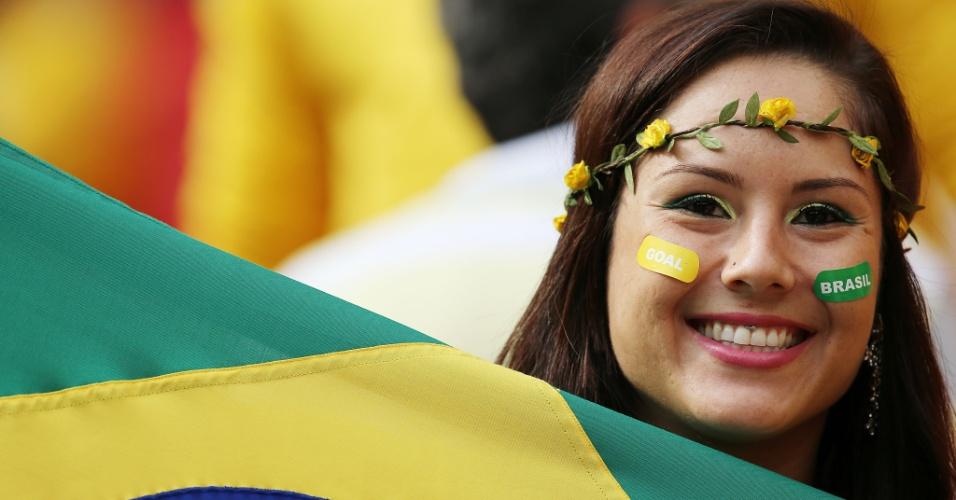 23.jun.2014 - Com acessórios e cores do Brasil, torcedora espera o início da partida contra Camarões
