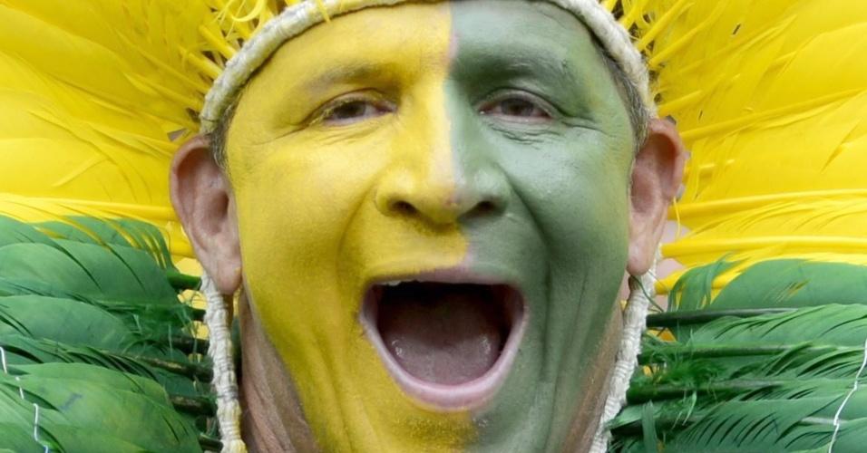 23.jun.2014 - Torcedor brasileiro pinta o rosto e usa cocar verde e amarelo para acompanhar jogo do Brasil contra Camarões, no Estádio Mané Garrincha