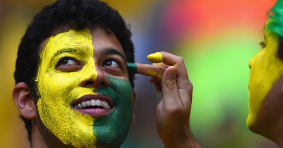 23.jun.2014 - Brasileiro pintas as cores do país antes do jogo contra Camarões, no Mané Garrincha