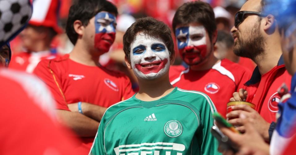 Garoto palmeirense pinta o rosto com as cores do Chile para assistir à partida contra a Holanda, no Itaquerão