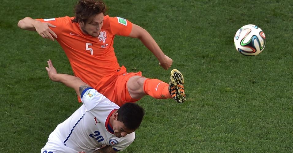 Holandês Daley Blind ergue o pé para tirar a bola da cabeça de Charles Aranguiz