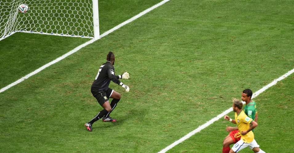 23.jun.2014 - Neymar observa a bola entrar enquanto o goleiro Charles Itandje, de Camarões, não consegue evitar o primeiro do Brasil no Mané Garrincha