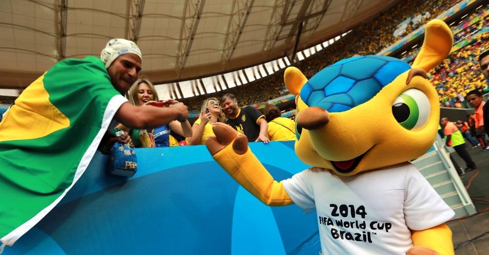 23.jun.2014 - Torcedor brinca com o mascote Fuleco no gramado do estádio Mané Garrincha, em Brasília