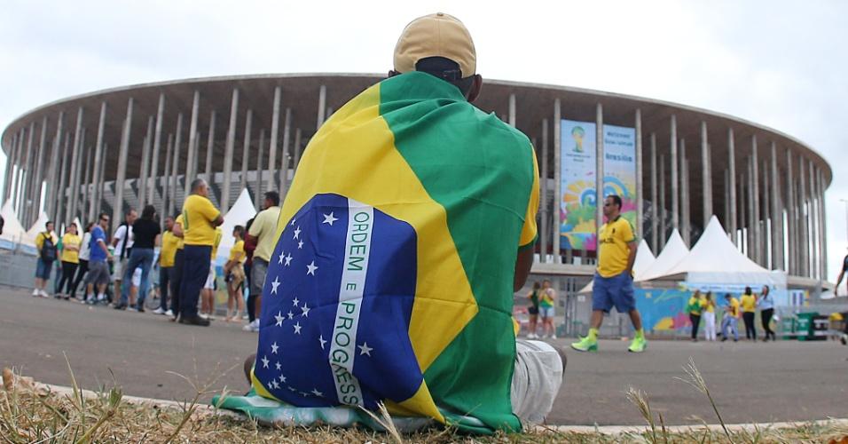 Torcedor coberto por bandeira brasileira aguarda a abertura dos portões do estádio Mané Garrincha
