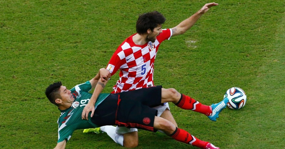 Vedran Corluka, da Croácia, puxa a camisa de Oribe Peralta, do México, durante dividida