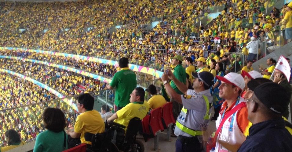 23.jun.2013 -- Policial militar aproveita área reservada para cadeirantes para tirar fotos com o celular e assistir à goleada do Brasil sobre Camarões por quatro a um, nesta segunda-feira no estádio Mané Garrincha, em Brasília