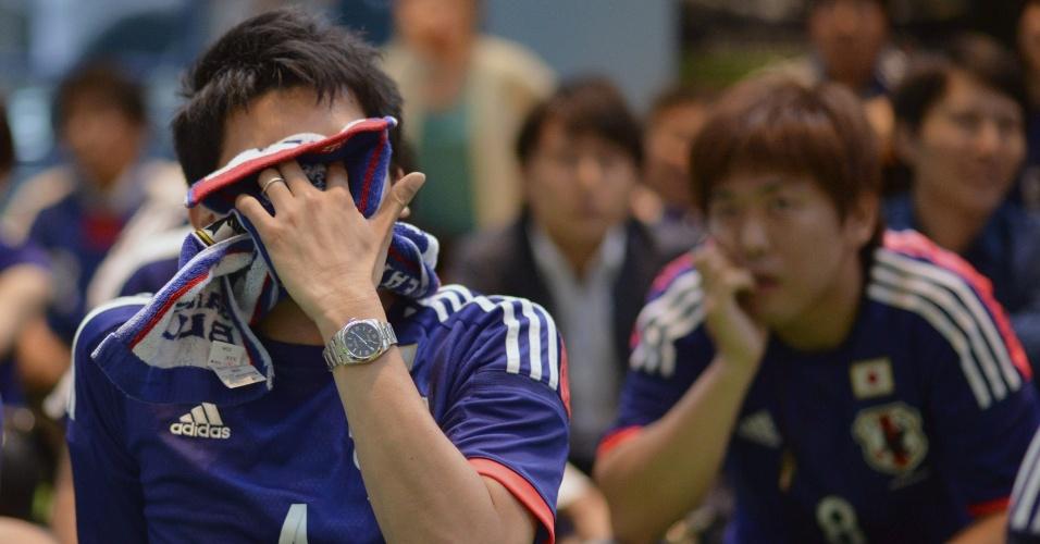 24.jun.2014 - Japoneses lamentam em Tóquio mais uma derrota do Japão e eliminação na Copa do Mundo