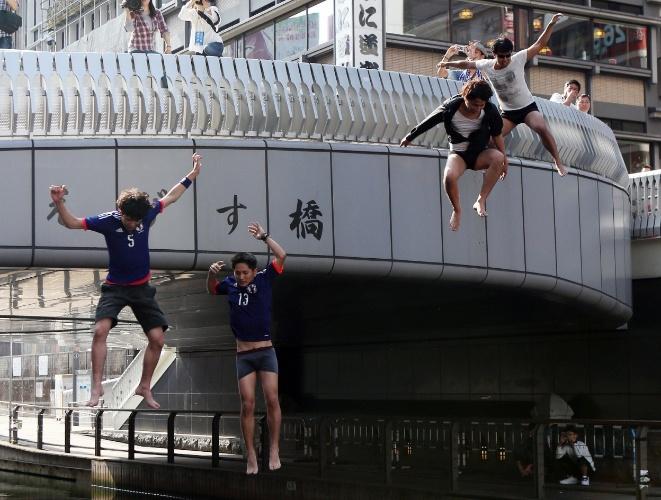 24.jun.2014 - Japoneses pulam em rio na cidade de Osaka após eliminação da seleção nacional da Copa do Mundo