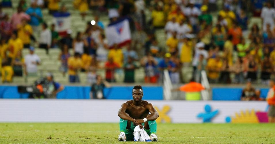 Abatido, Cheick Tiote fica sentado no gramado após a Costa do Marfim perder para a Grécia e ser eliminada da Copa do Mundo